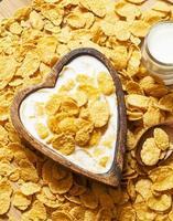 gesundes Frühstück: Cornflakes mit Milch in einer Holzschale foto