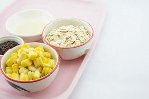 Mais, Hafer, Schokolade und gesüßte Kondensmilch auf rosa Tablett foto