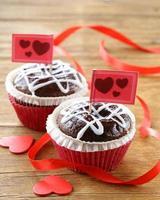festliches Gebäck zum Valentinstag, Schokoladenmuffin mit roten Herzen foto