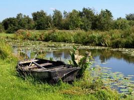 verlassenes Boot in der Nähe von Teich foto