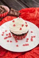 Schokoladen Cupcake mit roten Herzen verziert foto