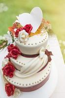 Hochzeitstorte mit essbarer Dekoration, die vom Sonnenlicht beleuchtet wird
