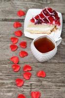 Tasse Tee, Stück Kuchen und rotes Herz