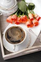Tasse Kaffee und ein Strauß Rosen