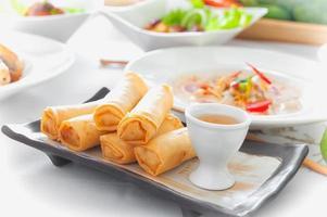 leckere thailändische Frühlingsrollen mit Sauce auf Teller foto
