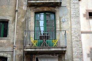 Balkon mit gelben Stühlen und Flaschen Wein