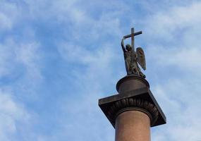 Engel mit Kreuz gegen bewölkten blauen Himmel foto