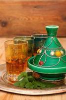 Tajine und marokkanischer Tee mit Minze auf einem Metalltablett foto