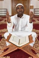 junger afrikanischer muslimischer Typ, der den Koran liest