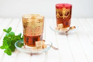 marokkanischer Tee mit Minze und Zucker in einem Glas foto