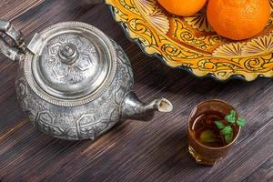 marokkanischer Tee mit Minze, Wasserkocher und Gericht mit traditioneller Verzierung foto