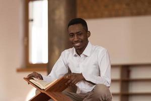 afrikanischer muslimischer Mann, der heiliges islamisches Buchkoran liest