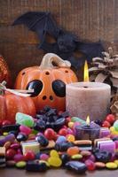 Halloween-Süßigkeiten mit Kürbissen auf dunklem Holzhintergrund.