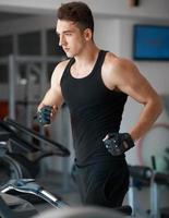 Sportler, der auf einem stationären Fahrrad trainiert foto