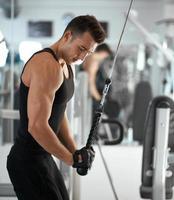 Mann, der im Trainer für Trizepsmuskeln trainiert foto
