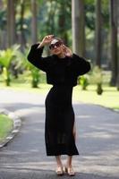 schöne asiatische Dame im schwarzen Kleid, posierend im Park foto