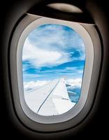 Blick durch Fensterflugzeuge während des Fluges im Flügel mit Blau foto