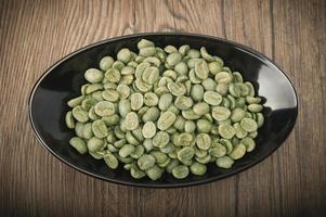 Tasse mit grünen Kaffeebohnen foto