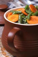 grüne Bohnen mit geschnittenen Karotten in einem Topf foto