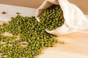 grüne Bohne im Sack auf Holzhintergrund foto