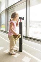 kleines Mädchen, das durch Fernglas im Wartezimmerfenster des Flughafens schaut foto