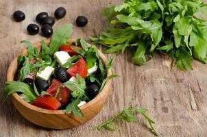 Griechischer Salat in einer hölzernen Salatschüssel auf dem Tisch foto