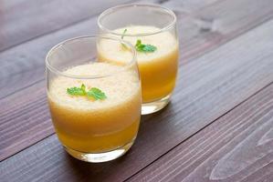 Ananassaft und Ananas auf Holztisch. für die Gesundheit foto