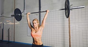 Gymnastikfrau, die Gewichte hebt foto
