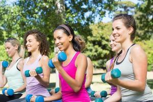 Fitnessgruppe, die Handgewichte im Park hebt foto