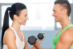 Paar hat Spaß beim Heben von Gewichten. foto