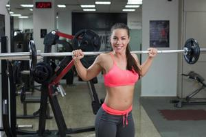 Fitness-Frau, die Gewicht im Fitnessstudio hebt