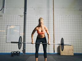 Gymnastikfrau, die schwere Gewichte im Fitnessstudio hebt foto