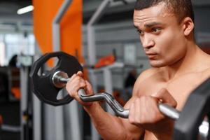 Porträt des Gewichthebers mit Langhantel in den Händen foto