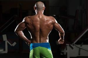 reifer muskulöser Mann, der Muskeln spannt foto