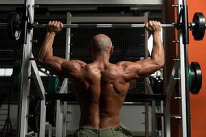 gesunder reifer Mann, der Übung für Schulter tut foto