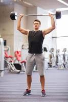 junger Mann, der Muskeln mit Langhantel im Fitnessstudio biegt