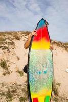 Der junge Surfer am Strand versteckt sich hinter seinem bunten Surfbrett foto