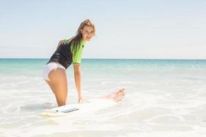 fröhliche hübsche Blondine bereitet sich auf das Surfen vor foto