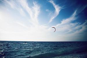 Menschen, die Kitesurfen auf klarem blauem tropischem Wasser genießen