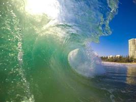 grüne glasige Welle, die am Strand bricht foto