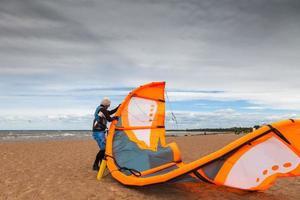Kitesurfer bereitet seinen Kite an einem windigen Tag vor foto