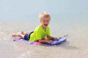 kleines Kind, das auf Boogie-Brett im Ozean reitet foto