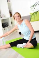 attraktive und gesunde junge Frau, die Fitnessübungen nach Hause macht foto
