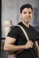 junger Mann, der Yogamatte trägt foto