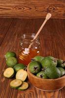 Feijoa Früchte und Bank von Honig auf einem Tisch foto
