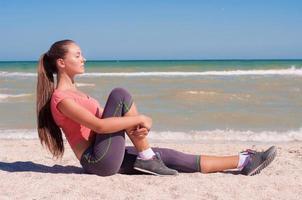 junge schöne Sportlerin, die Sport am Strand spielt foto