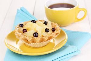 süßer Kuchen mit Tasse Tee auf hölzernem Hintergrund foto