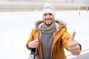 glücklicher junger Mann, der Daumen oben auf Eisbahn zeigt
