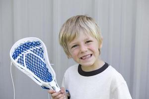 Junge mit einem Lacrosse-Stock foto