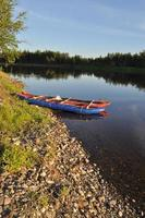 abendliche Flusslandschaft mit einem Boot am Ufer.